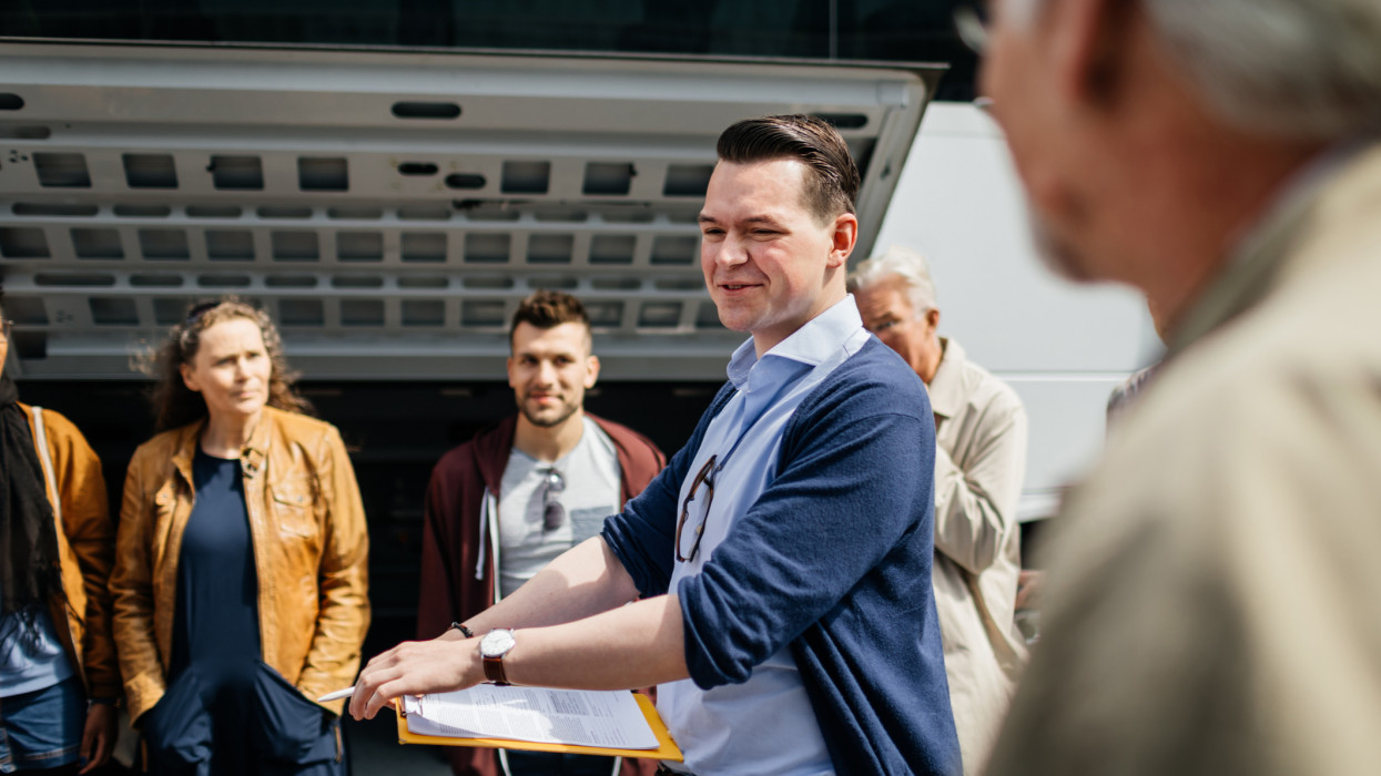 A travel rep discusses the details of the bus journey with holidaymakers before Departure.