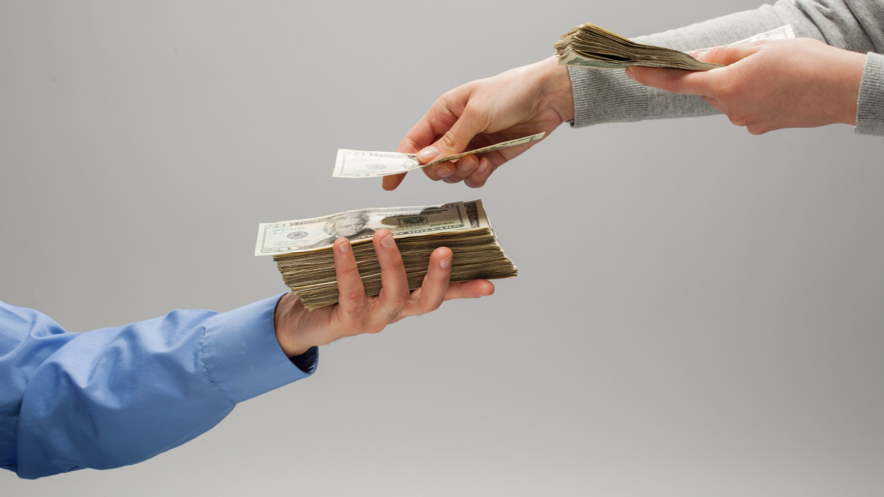 Womans hands placing US paper currency into mans hand