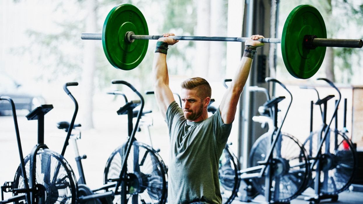 Man doing lunges with barbell overhead during workout in gym gym