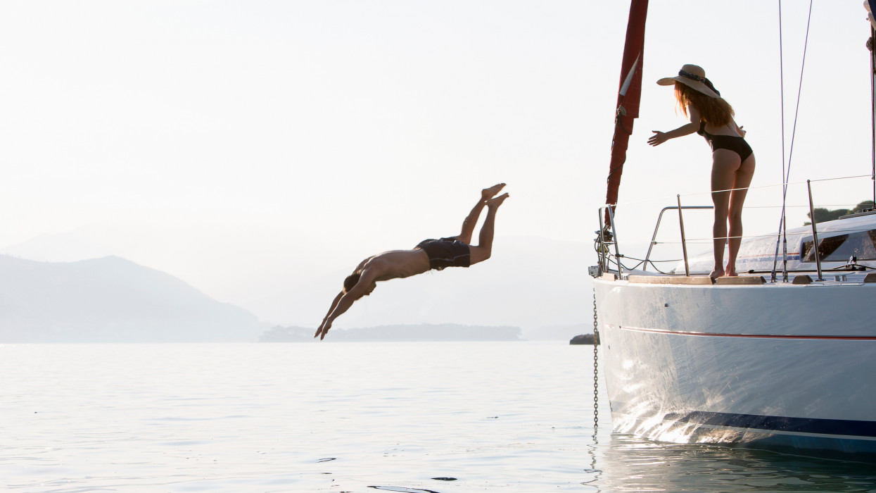 woman holds hands out in awe as man dives off yacht, low light