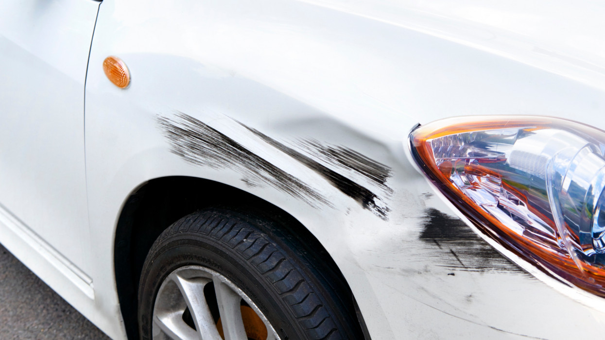 close up shot of generic car, with hit and run damage to its front wing