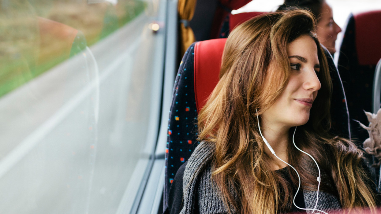 A young woman travelling with bus while listening music