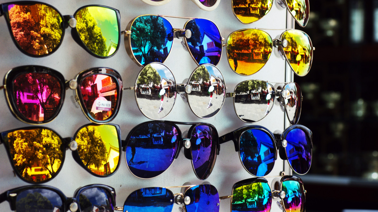 Selection of mirrored sunglasses on a retail display, outdoors.