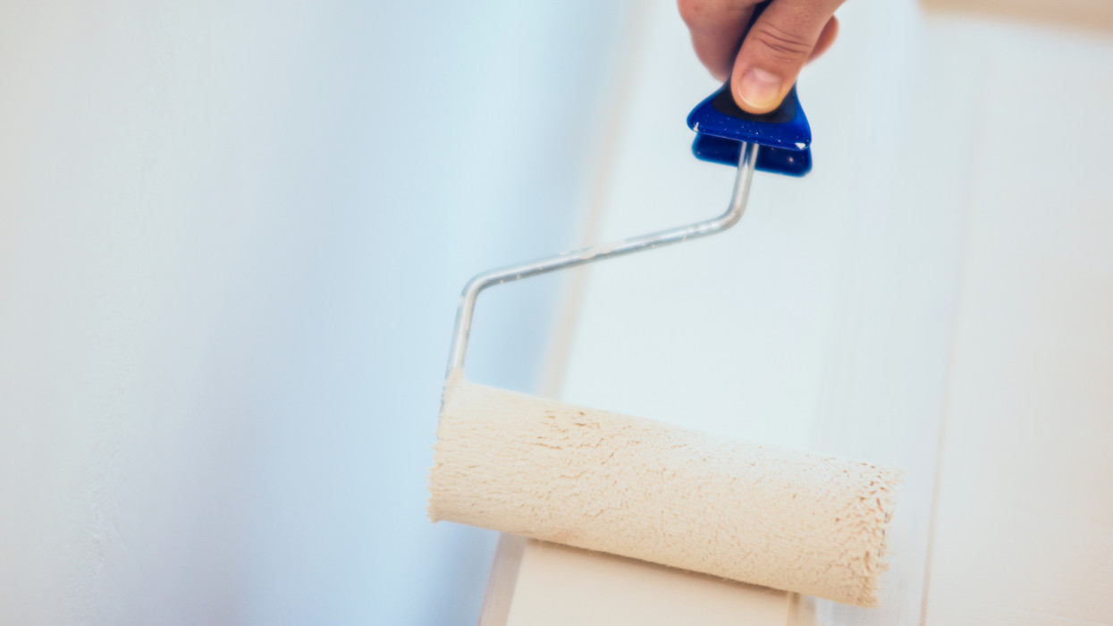Hand and paint roller in a white room painting a door.