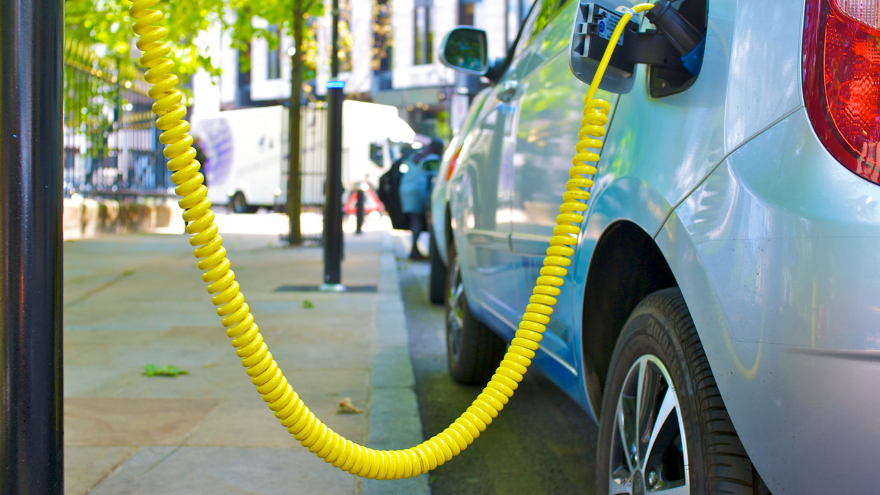An Eco Electric car is re-charged from city street power point.