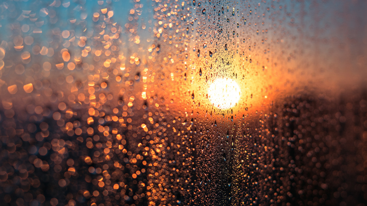 Wet Window with Condensation Water Against Sunrise or Sunset Glow in Cold Winter Day, Warm Indoor