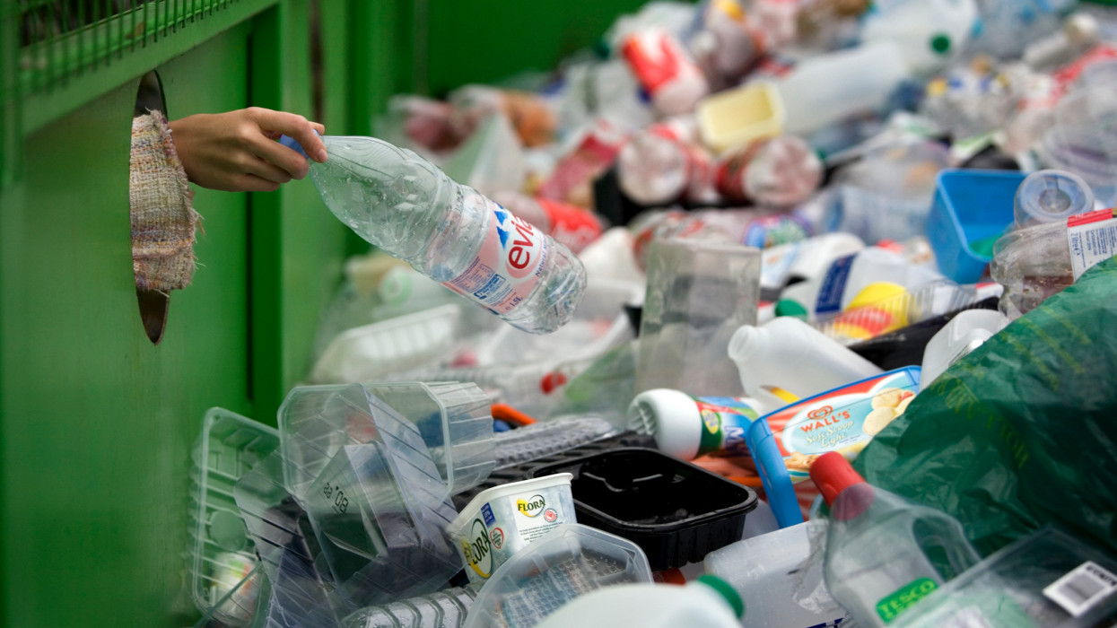 A woman depositing a plastic bottle in a recycling bin in Worcestershire, UK.