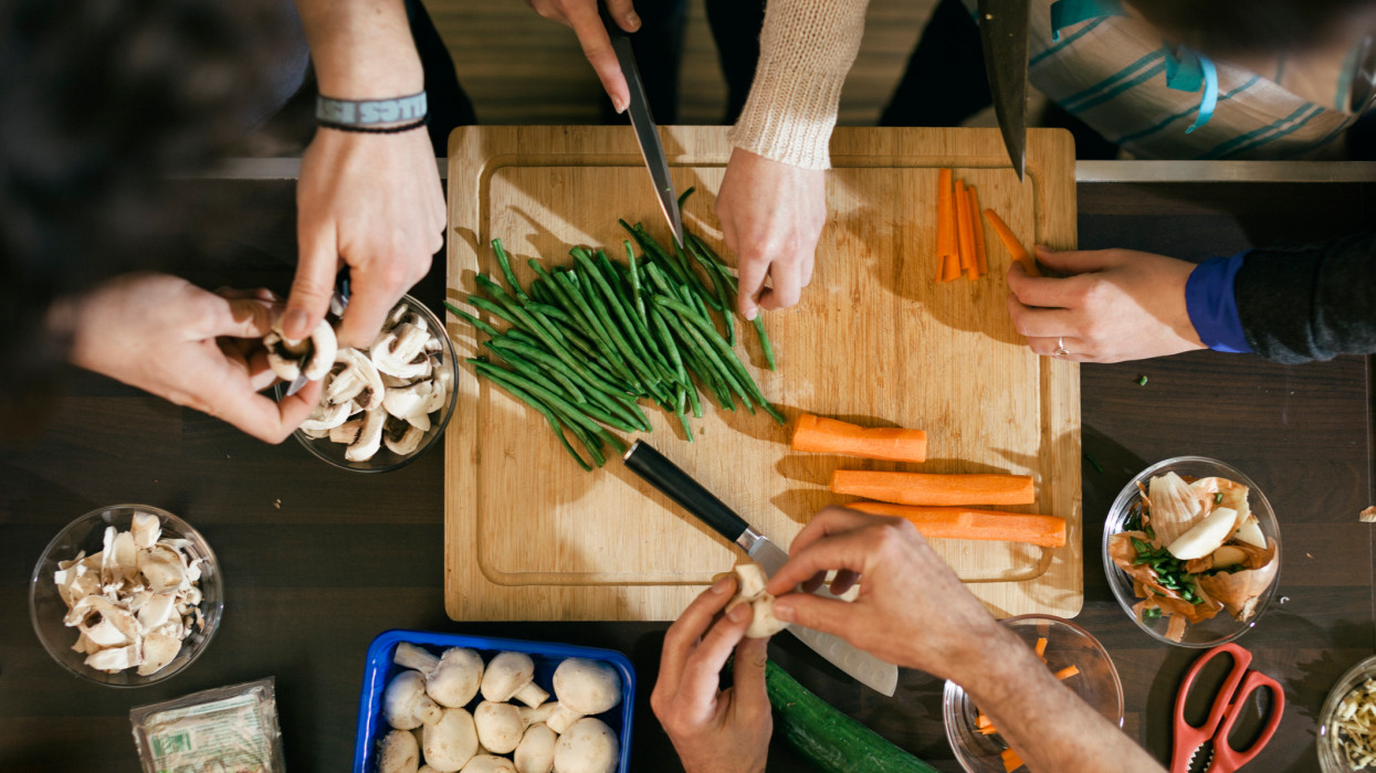 Close up of hands cutting vegetables on a wooden board in cooking class. Food like beans, carrots and mushrooms are getting ready to be cooked on a kitchen desk.