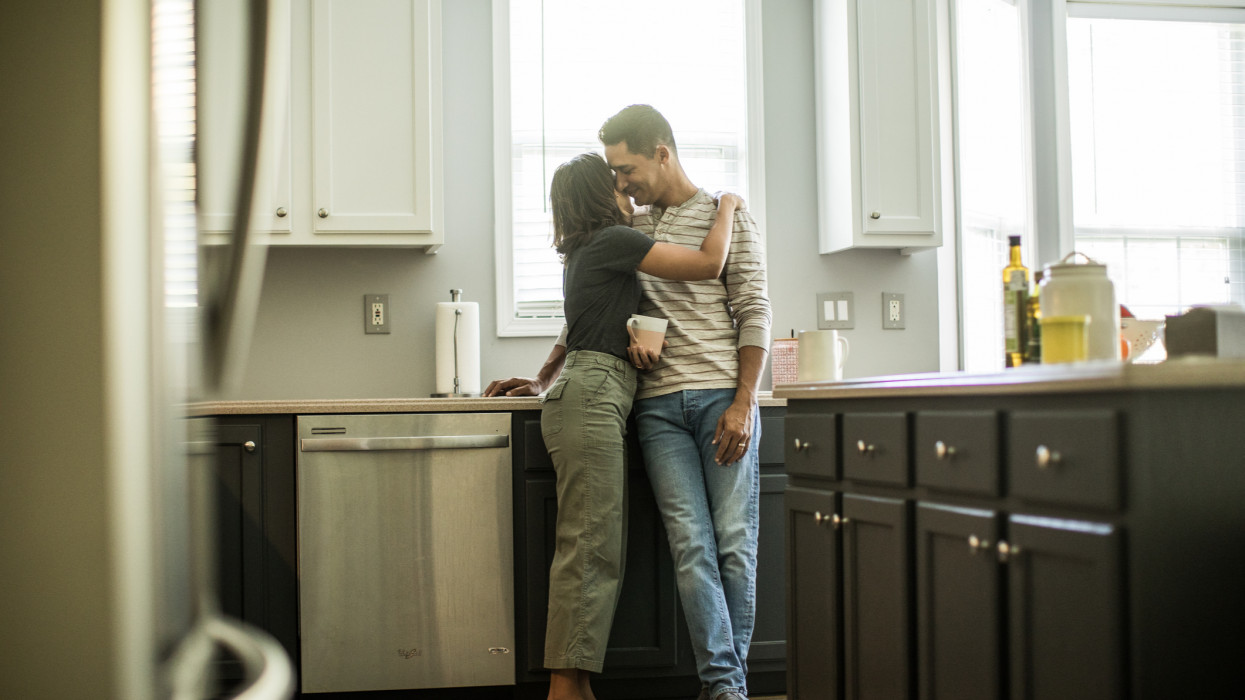 Husband and wife talking in kitchen