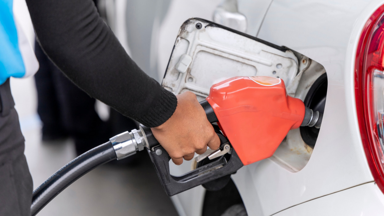 Hand holding fuel nozzle to refuel gasoline for car at the petrol station.