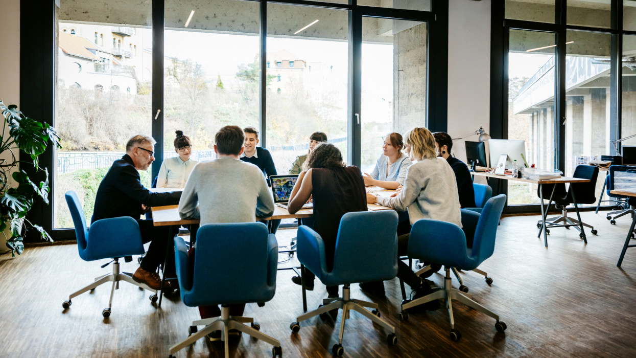 New business meeting with a group of entrepreneurs on a conference table in a modern office loft