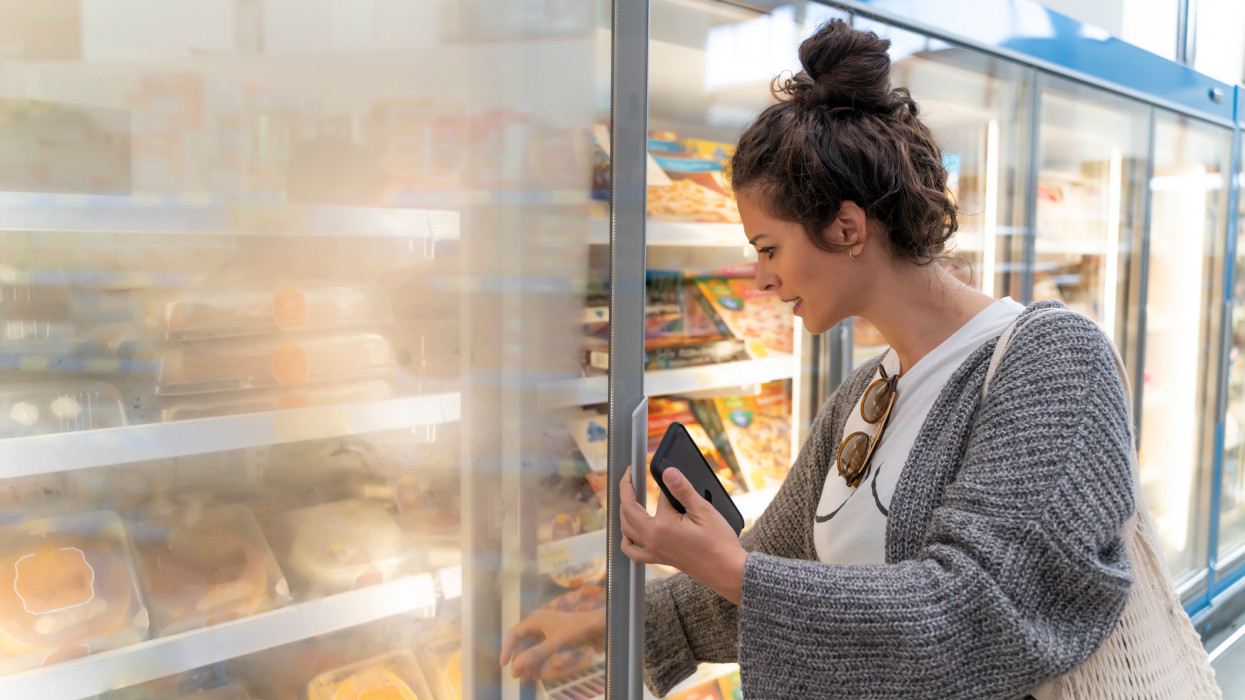 Young women customer searching in in frozen food case