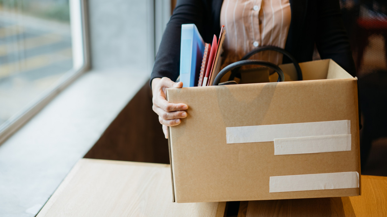 Asian woman holding cardboard box containing personal belongings after being fired by employer