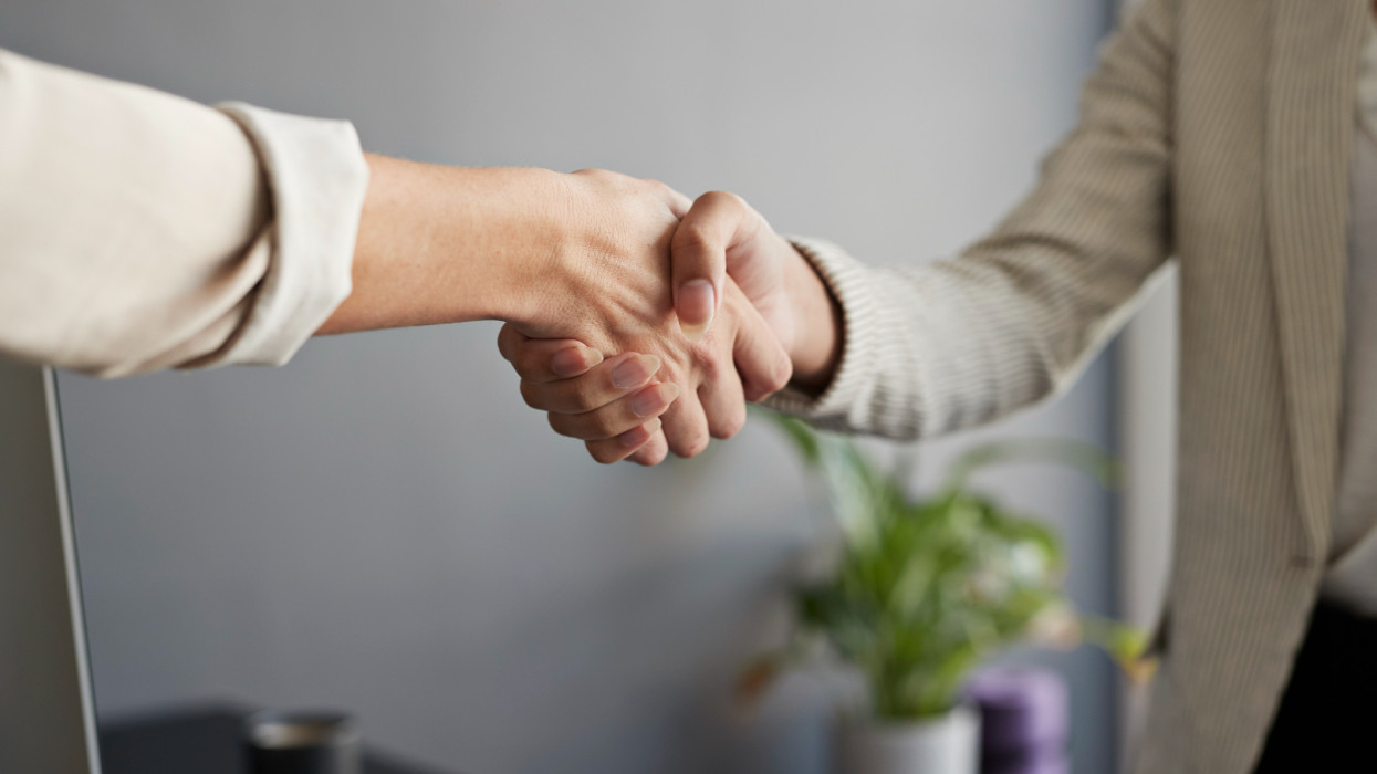 Midsection of female entrepreneur shaking hands with coworker at workplace cimlapi