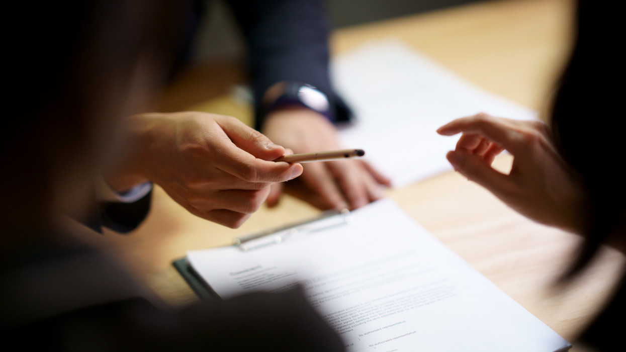 Selective focus shooting on hand of Businessman giving pen to Partnership to sign contract agreement in document