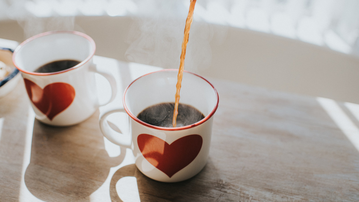 Pouring black coffee into coffee cups with heart design. Space for copy. Conceptual.