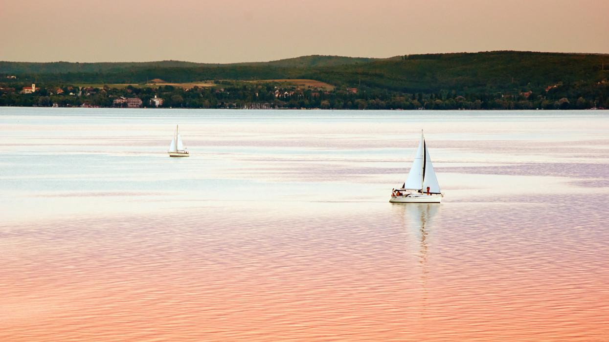 Balaton lake with reflecting white boats in sunset