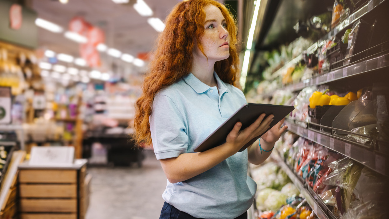 Woman using a digital tablet while doing inventory in a grocery store. Female trainee employee working in supermarket.