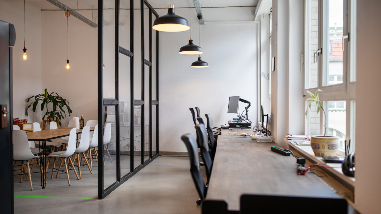 Creative workplace interior with over hanging lamps. Interior of coworking workplace.