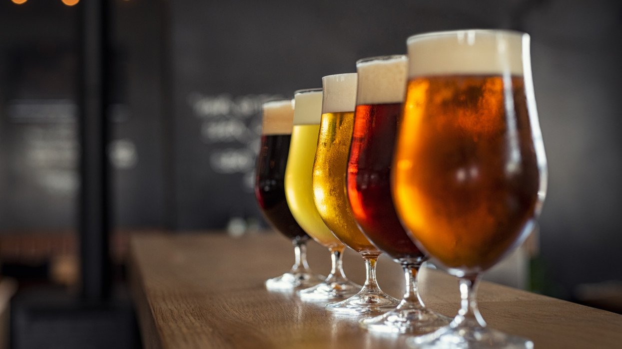Glasses with different sorts of craft beer on wooden bar. Tap beer in pint glasses arranged in a row. Closeup of five glasses of different types of draught beer in a pub.