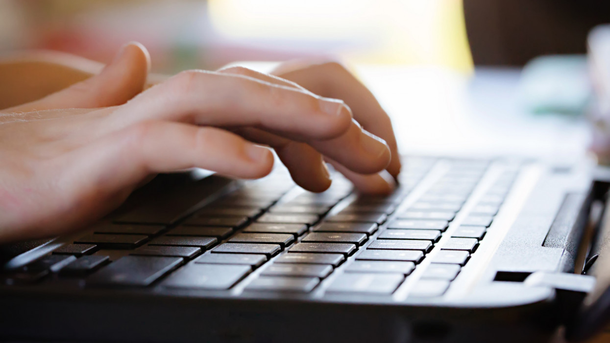 A childs hands typing on a computer laptop keyboard