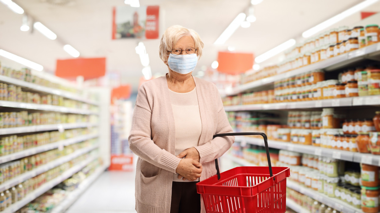 Senior female customer with a shopping basket in a supermarket wearing a protective medical mask