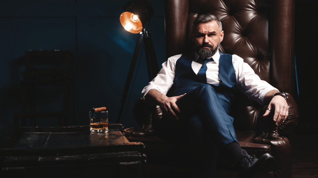 Portrait of handsome elegant mature man with cigar and a glass whiskey in a dark room