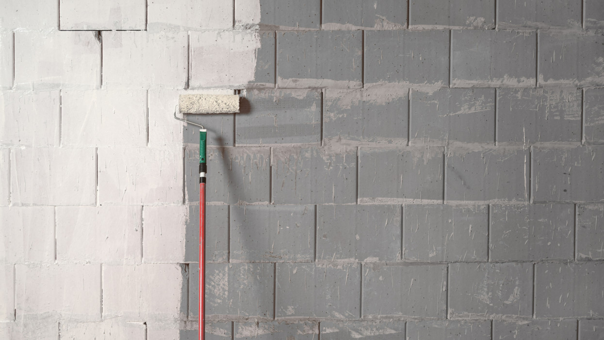 Roller is painting a rough wall of grey stones with white paint, background concept for constriction, building and renovation, copy space