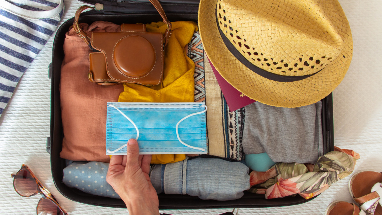Hand putting a face mask on the suitcase prepared to travel in summer, in the new normal, after the coronavirus covid 19 pandemic. There are other accesories like a hat, a camera and a bikini. Concept of quarantine, coronavirus, summer vacation in new normal. Flat lay or top view