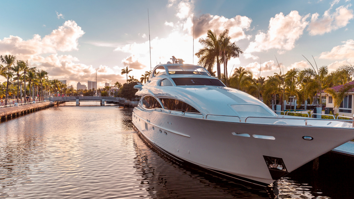 Front view of the sun coming down at Fort Lauderdale canals. Abbreviated Ft. Lauderdale is known as the Venice of America, due to its extensive and intricate canal system. Yachts moored on canal against cloudy sky at sunset in Las Olas Boulevard, Fort Lauderdale. Las Olas Boulevard is the main touristic street and is sorrounded by canals, luxury yachts and amazing residential houses.