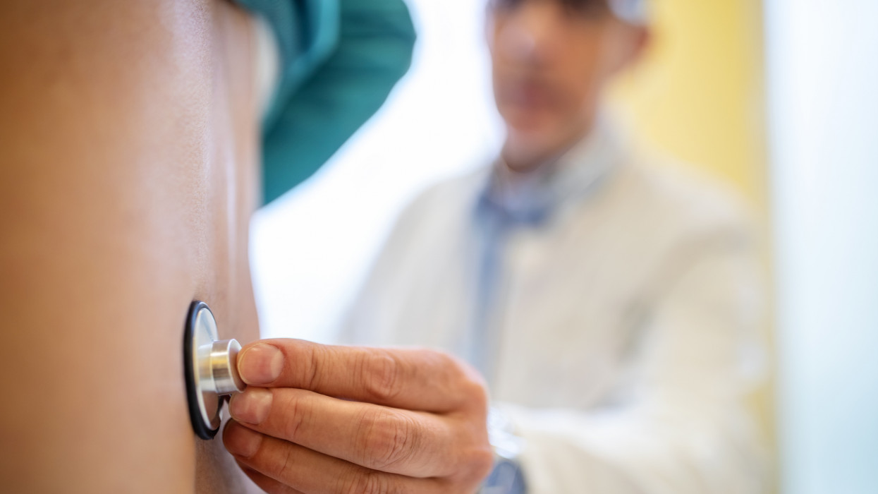 Close-up shot of a doctor examining male patients back with stethoscope in clinic. Medical professional checking senior patient in examination room.