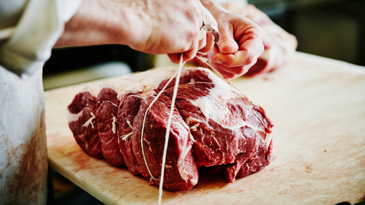 Butcher tying up beef bottom round at counter in butcher shop