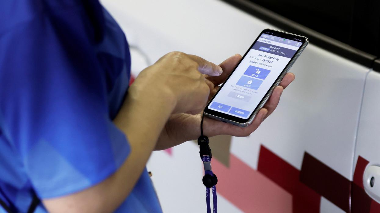 Tokió, 2021. július 1.A világméretû koronavírus-járvány miatt 2021-re halasztott 2020-as tokiói nyári olimpiát és paralimpiát elõkészítõ bizottság munkatársa a sofõrnek készített okostelefonos alkalmazással kinyit egy Toyota Prius hibridautót a személyzet olimpia alatti közlekedését támogató rendszer tokiói bemutatóján 2021. július 1-jén.MTI/EPA/Bloomberg/Ota Kijosi