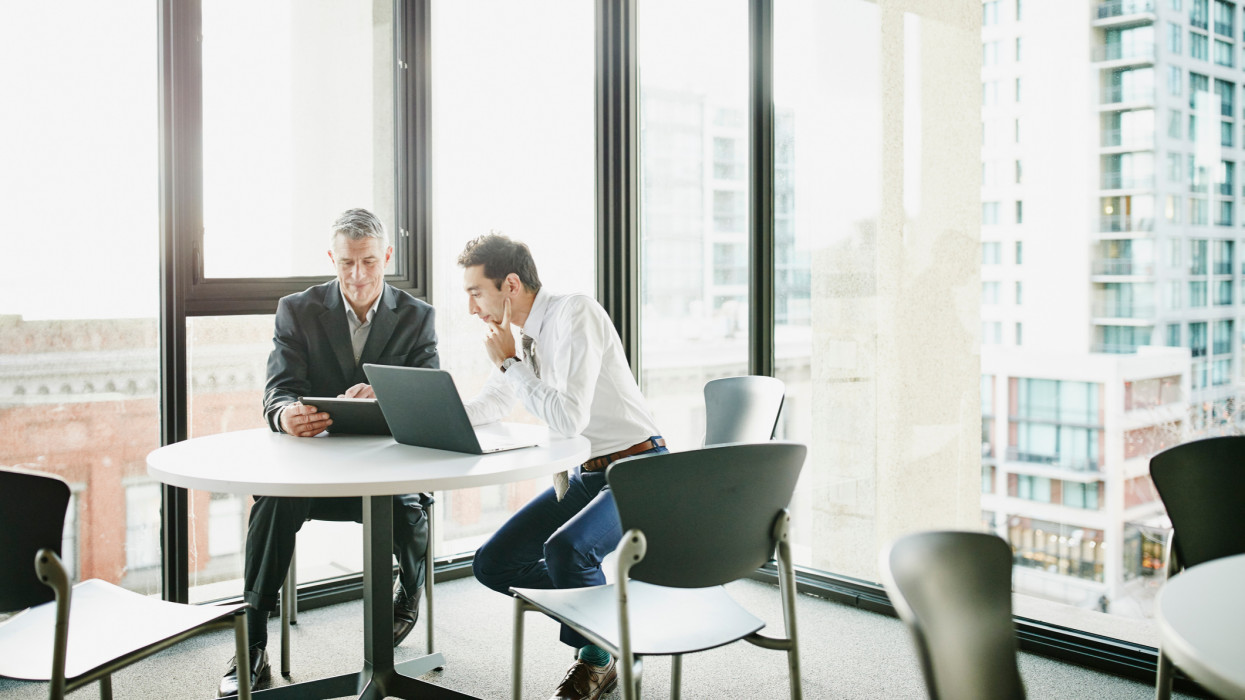Businessmen reviewing data on digital tablet in office