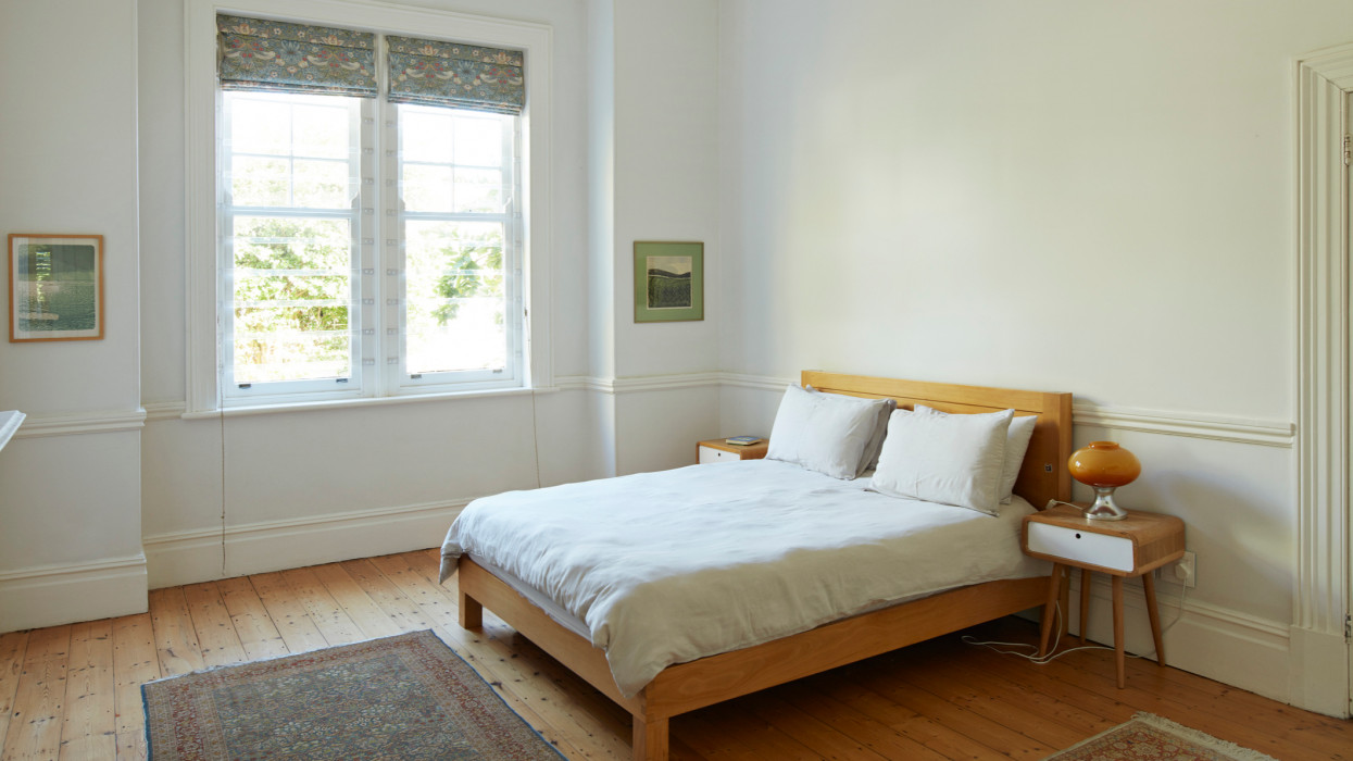 Wooden bed by window in bedroom at home