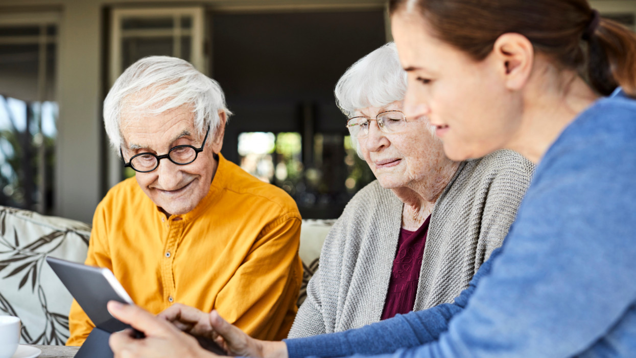 Caregiver discussing with senior couple over digital tablet. Elderly male and female are sitting with nurse at home. They are sitting in balcony.