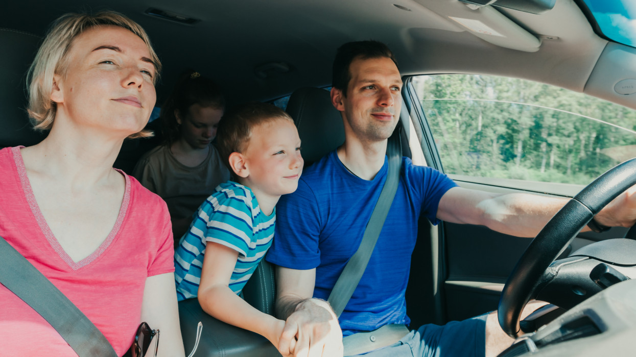 Smiling family with kids sitting in the car and driving.