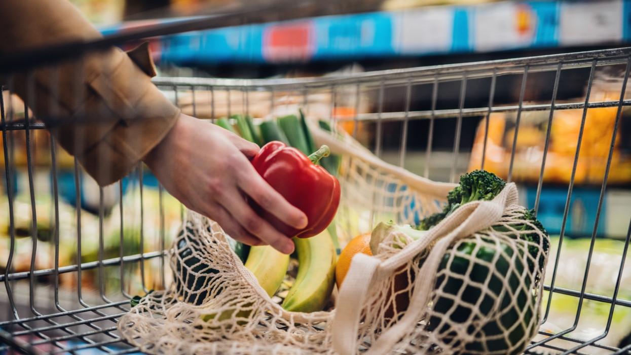 Close-up shot of female hand putting a red bell pepper into a mesh grocery bag. Shopping with eco-friendly shopping bag for a sustainable lifestyle.