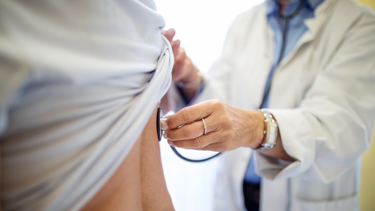 Cropped of female doctor examining patient. Medical professional checking womans back with stethoscope in clinic.