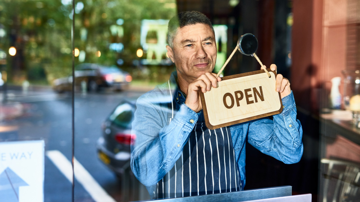 Mature man in his 40s holding open sign on door of business, looking through window, optimism, aspiration, resilience