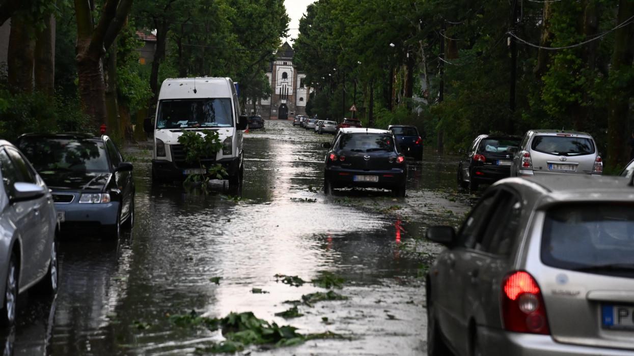 Budapest, 2021. július 9.Autók haladnak a felhõszakadás után esõvízzel elárasztott, letört faágakkal teli úton Budapesten, Wekerletelepen 2021. július 9-én. Az esõzés miatt több kerületben is korlátozásokra kell készülniük az autósoknak és a tömegközlekedéssel utazóknak.MTI/Mihádák Zoltán