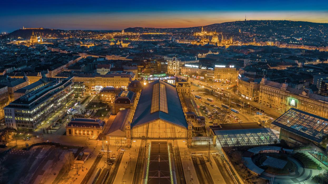 Budapest, Hungary - Aerial panoramic skyline view of Budapest at dusk with illuminated Western Railway Station, Parliament, St. Stephens Basilica, Buda Castle Royal Palace and Fishermans Bastion