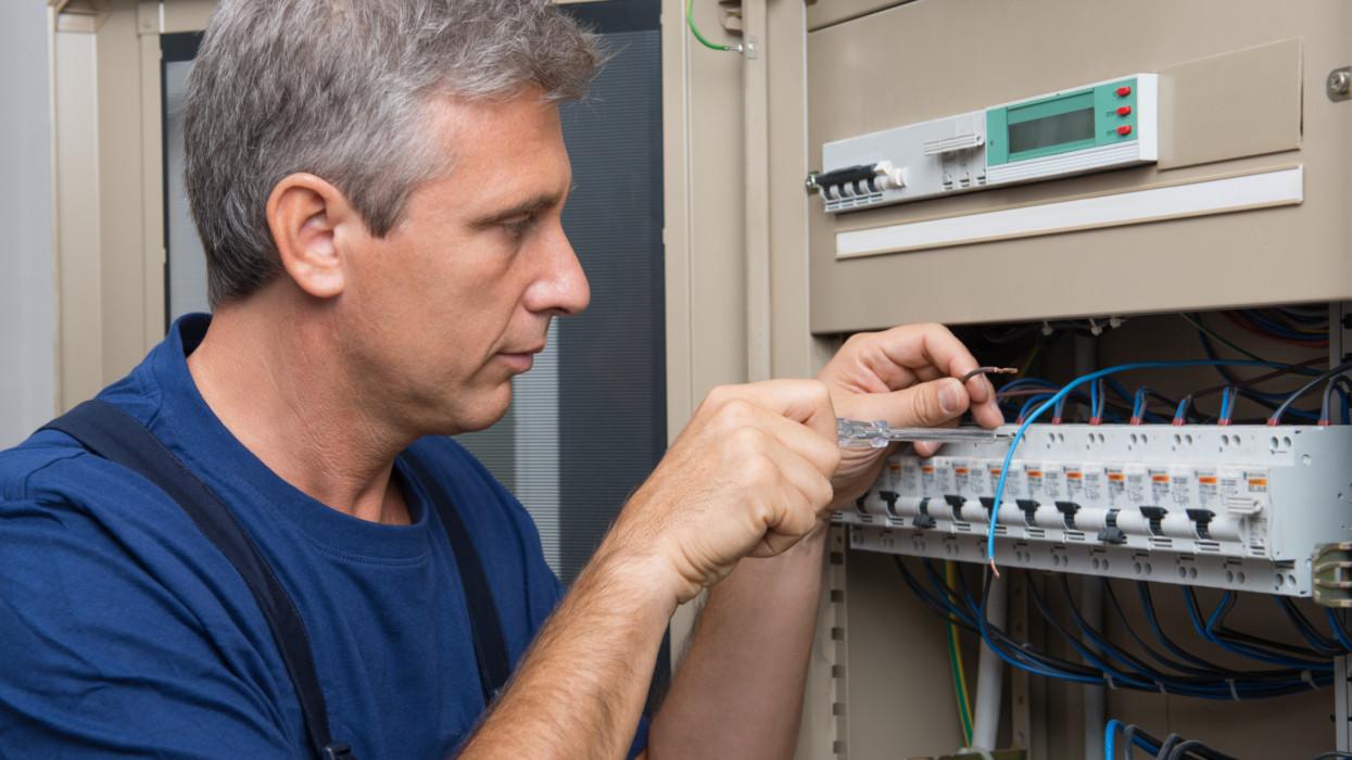 Repairman Fixing An Electric Switchboard Indoor