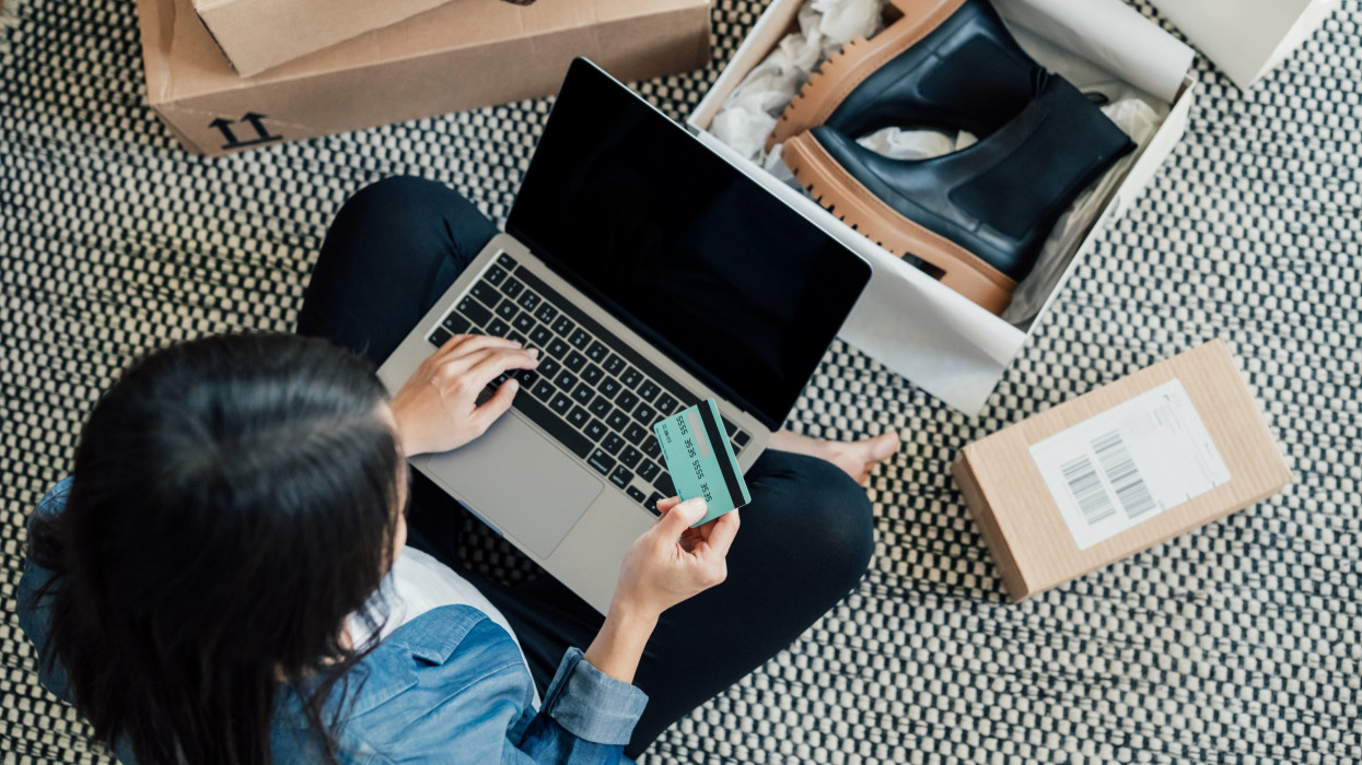 High angle view of a young Asian woman shopping online on laptop, making payment with credit card. Enjoying Seasonal sales. Shopaholic concept.