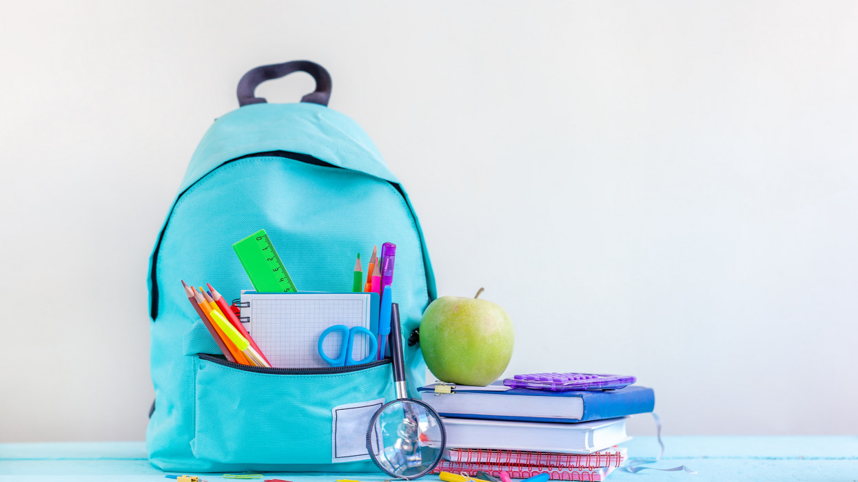 Full turquoise School Backpack with stationery on table. Concept back to school.