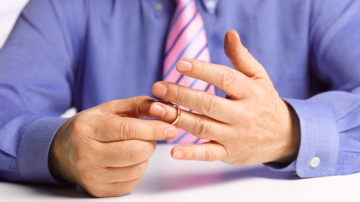 businessman removing wedding ring before being unfaithful