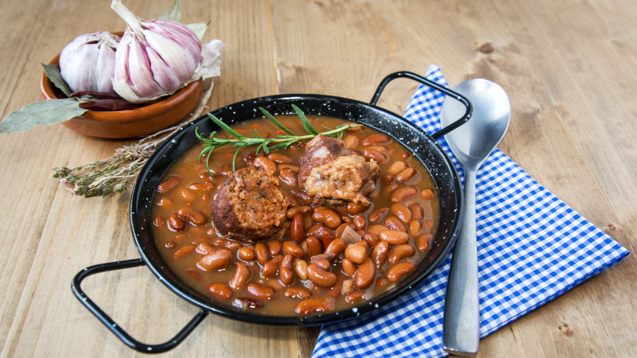 Traditional Spanish stew of white beans on old wooden tableTraditional Spanish stew of white beans on old wooden table
