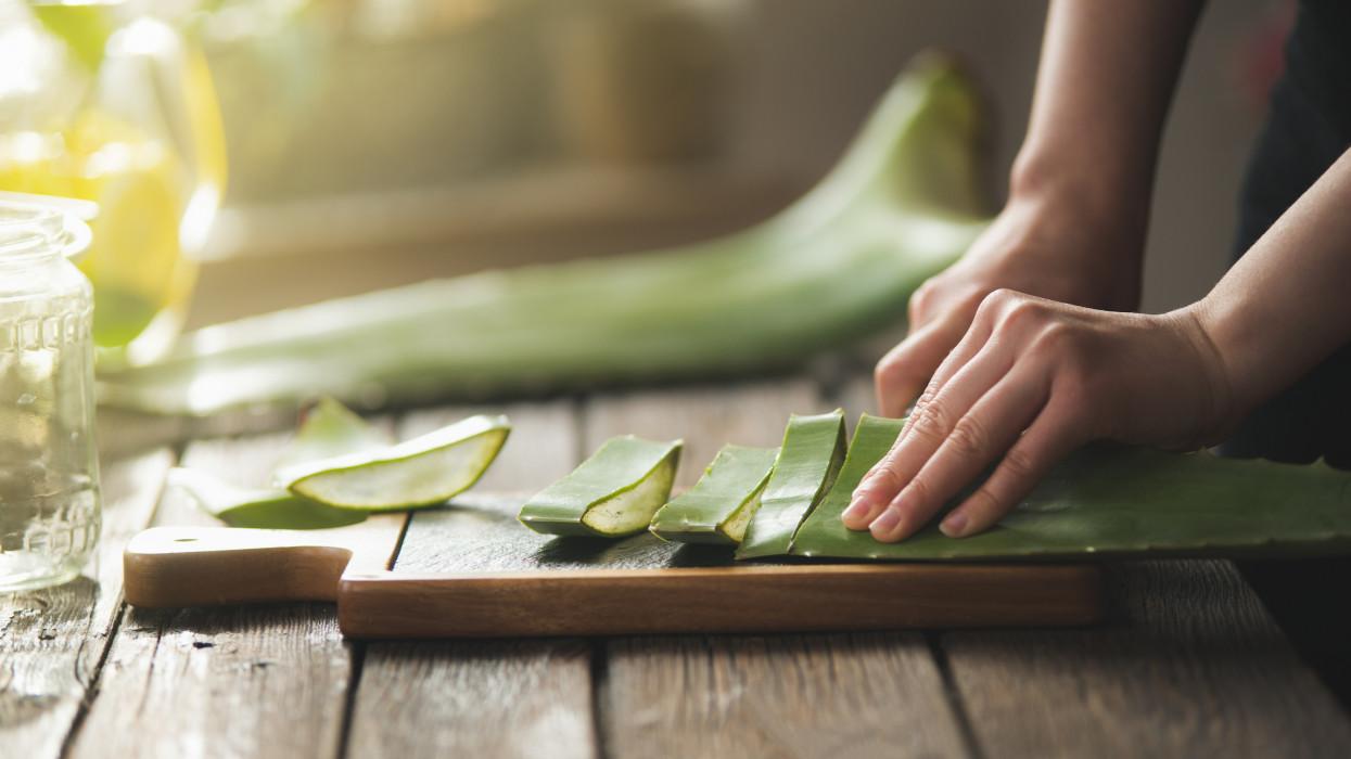 Women hands preparing fresh big Aloe Vera leaf on rustic cutting board. Step by step.  Aloe Vera gel making