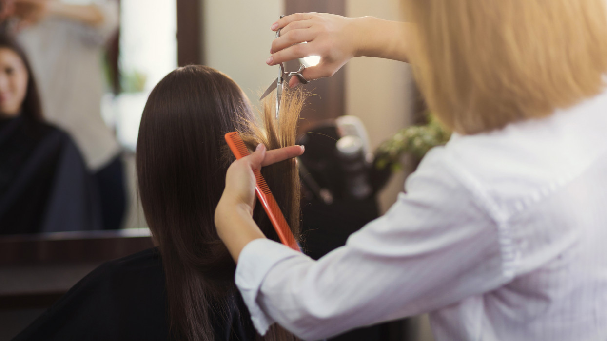Professional hairdresser trimming long brown hair with scissors in beauty salon