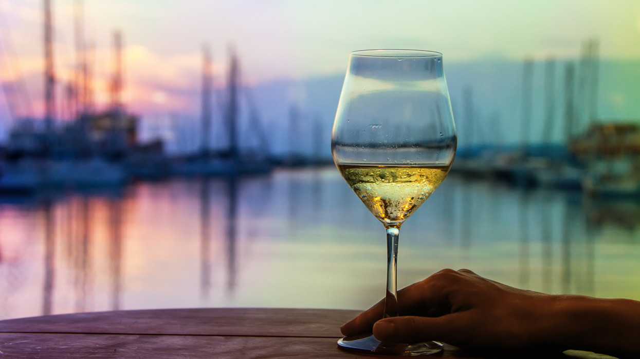 Glass of white wine and female hand a background of the sunset sky in port of yacht-club